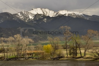 Small Farm by River in front of Snow Mountains