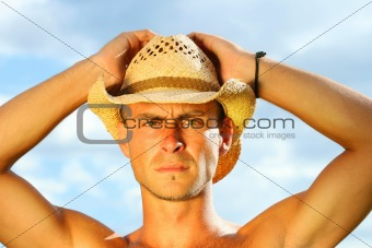 Young man with hat against a blue sky