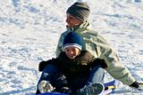 Happy Mother and Son Sledding down the Hill
