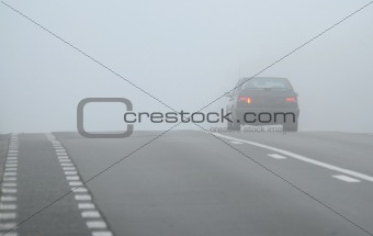 Car disappearing through fog