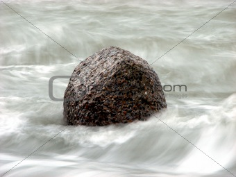 Single rock surrounded by waves