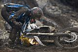 Muddy Enduro rider picking up bike after fall