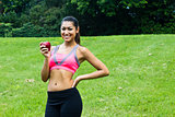 Fit young woman with an apple in the park