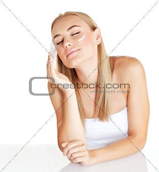 Beautiful female using moisturizer