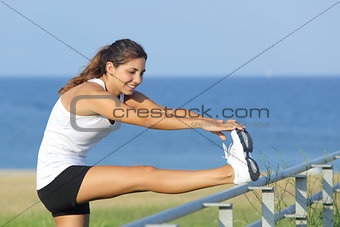 Beautiful sportswoman stretching with the sea in the background