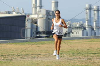 Beautiful woman running on the grass with a factory in the background