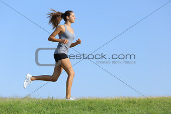 Beautiful woman running on the grass with the sky in the background