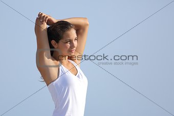 Beautiful woman stretching with the sky in the background