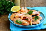 shrimp cooked with lemon and basil on a wooden table