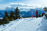 Family walking on winter mountain slope