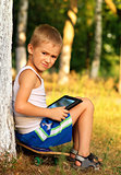 Boy Child playing with Tablet PC sitting on skateboard Outdoor with forest on background Game Dependence concept