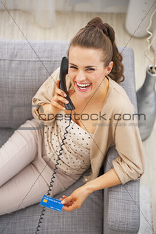 Smiling young woman with credit card sitting on sofa and talking