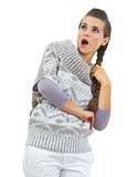 Surprised young woman in sweater looking on copy space