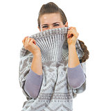 Young woman hiding in sweater neckline