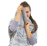 Smiling young woman hiding in sweater neckline