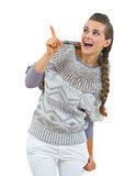 Surprised young woman in sweater pointing on copy space