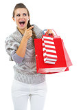 Surprised young woman in sweater with shopping bags pointing on