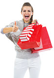 Surprised young woman in sweater with shopping bags showing thum