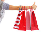 Closeup on young woman hand with christmas shopping bags showing