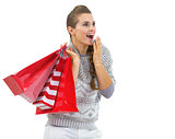 Surprised young woman in sweater with christmas shopping bags lo