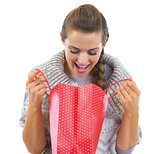 Happy young woman in sweater looking in christmas shopping bag