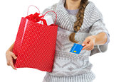 Closeup on credit card in hand of young woman in sweater with ch