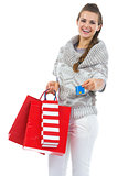 Smiling young woman in sweater with christmas shopping bag givin