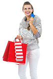 Thoughtful young woman in sweater with christmas shopping bag an