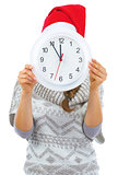 Young woman in sweater and christmas hat hiding behind clock