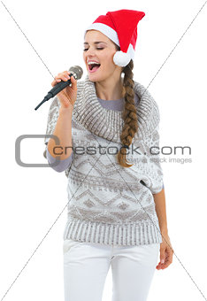 Happy young woman in sweater and christmas hat singing in microp