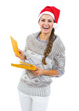 Happy young woman in sweater and christmas hat holding christmas