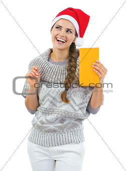 Thoughtful young woman in sweater and christmas hat holding lett