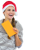 Happy young woman in sweater and christmas hat with letter looki