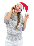 Happy young woman in sweater and christmas hat talking mobile ph