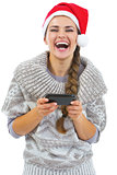 Happy young woman in sweater and christmas hat reading sms