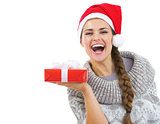 Happy young woman in sweater and christmas hat showing christmas