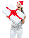 Happy young woman in sweater and christmas hat with big christma