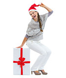 Happy young woman in sweater and christmas hat sitting on big ch