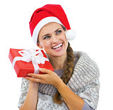 Smiling young woman in sweater and christmas hat shaking christm