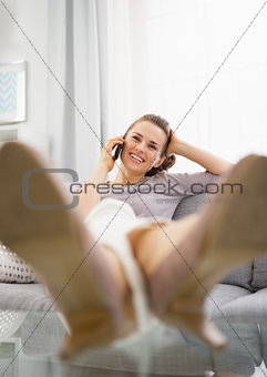 Happy young woman talking mobile phone in living room