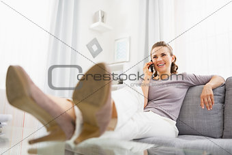 Smiling young woman talking cell phone in living room