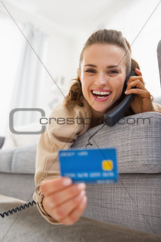 Happy young woman with credit card laying on sofa and talking ph