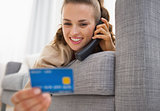 Young woman with credit card laying on sofa and talking phone