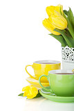 Yellow tulips and two tea cups