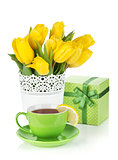 Yellow tulips, tea cup and gift box