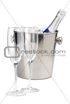 Champagne bottle in ice bucket and two empty glasses