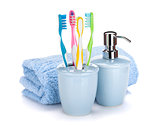 Four colorful toothbrushes, liquid soap and towel