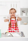 Happy little girl washing the dishes