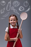 Young girl with apron and large wooden spoon