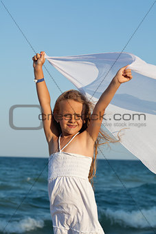 Little girl on sea shore playing with a kerchief in the wind